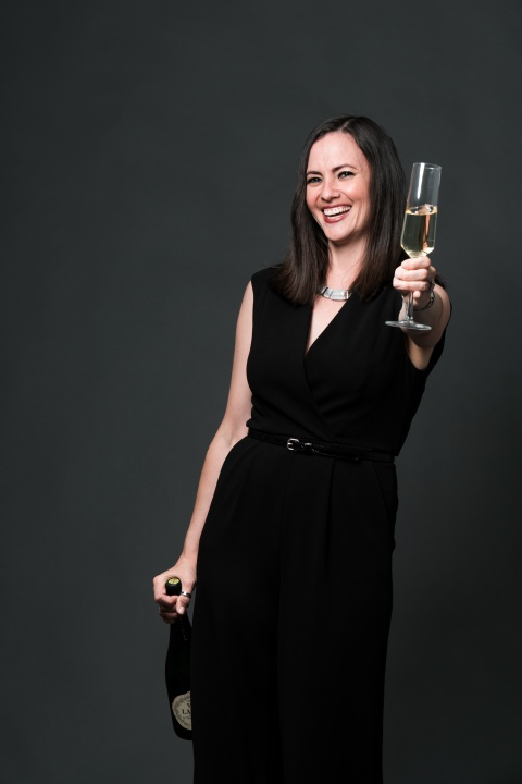 Chloe holding champagne out to toast